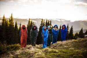 group of hikers jumping in sleeping bags in mountains